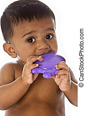Sweet Indian baby chewing on toy