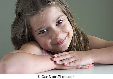 Sweet Innocence - a beautiful little girl smiling, with her...