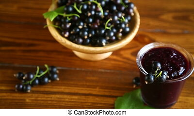 sweet jam of black currant berries on a wooden table