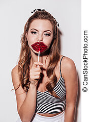 Sweet kiss. Beautiful young woman holding a lollipop in front of her mouthwhile standing against white background
