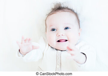 Sweet laughing baby girl in a knitted sweater