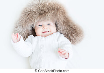 Sweet laughing baby in a big fur hat