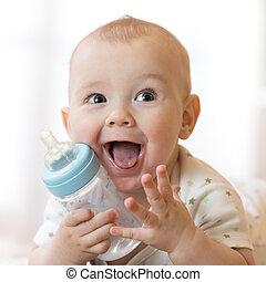 Sweet little baby holding plastic bottle