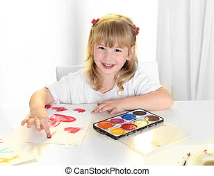 sweet  little blonde girl painting red hearts with fingers