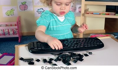 Sweet little child boy girl playing with broken keyboard...