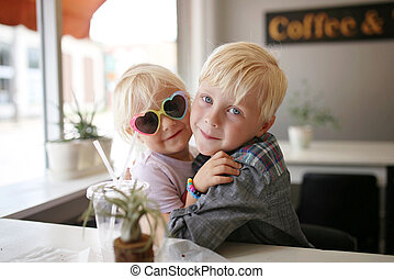 Sweet Little Child Hugging his Baby Sister at A Coffee House Cafe