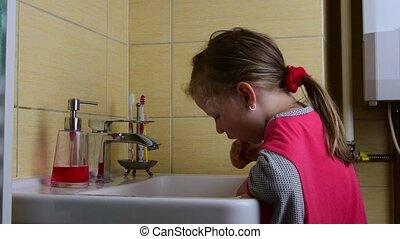 Sweet little girl brushes teeth in the bathroom. Preschool...