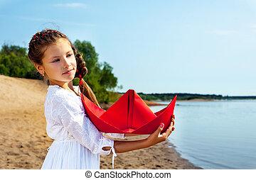 Sweet little girl cuddles paper boat