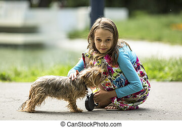 girl on the street with a small dog