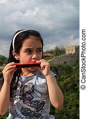 Sweet little girl playing harmonica