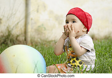 Sweet little girl playing with a ball
