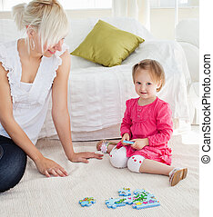 Sweet little girl playing with her mother
