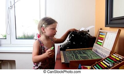 Sweet little girl plays with abacus and writes on blackboard with chalk. Preschool concept, childhood concept. Toy abacus with Czech alphabet and vintage typewriter. Cute girl like preschooler