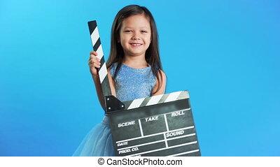 Sweet little girl with cinema clapper board on blue ...