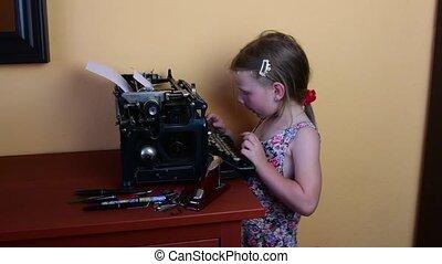 Sweet little girl writes on vintage typewriter. Preschool concept, childhood concept. Cute girl like preschooler
