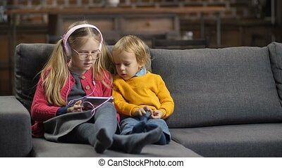 Sweet little siblings using tablet pc on sofa