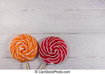 Sweet lollipops on white wooden background. Top view