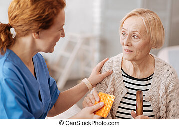 Sweet mature woman receiving prescribed pills - This will...