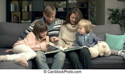 Sweet Memories - Family of four cuddling on sofa in living...