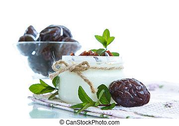 sweet milk yogurt with prunes in a glass jar