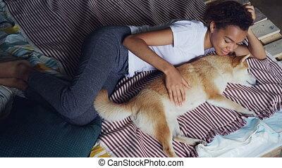 Sweet mixed race girl is stroking purebred shiba inu dog...
