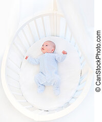 Sweet newborn baby boy in a white round crib with canopy