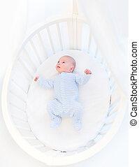 Sweet newborn baby boy in a white round crib with canopy