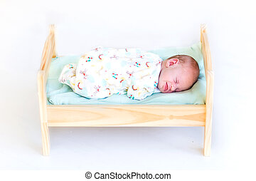 Sweet newborn baby sleeping in a toy bed