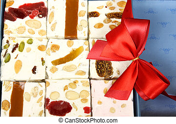 Nougats with dried fruits, caramel and nuts in decoration box with ribbon