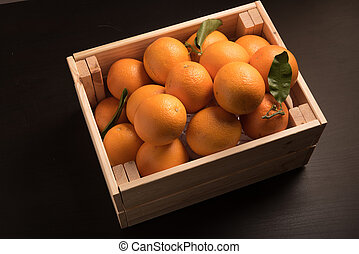 sweet orange in wooden box isolated on black background