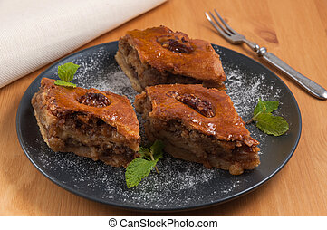sweet Oriental dessert baklava with nuts on a dark plate
