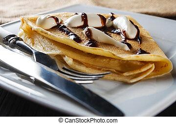 Sweet pancake with chocolate sauce and yogurt