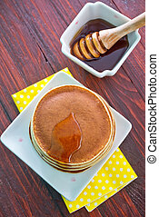 sweet pancakes with honey on the plate
