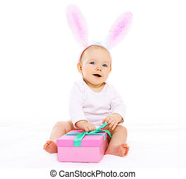 Sweet pink baby sitting in costume easter bunny with fluffy ears and gift box