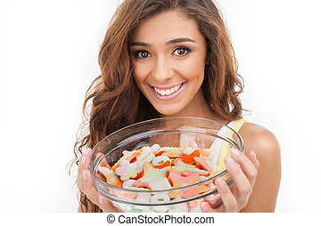 Sweet plate. Beautiful young women holding a plate full of candies while isolated on white