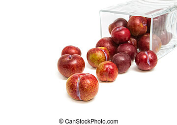 Sweet plums in glass jar on white background