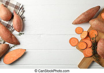 Sweet potato, board and towel on white wooden background, top view