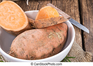 Sweet Potato (close-up shot) on rustic wooden background