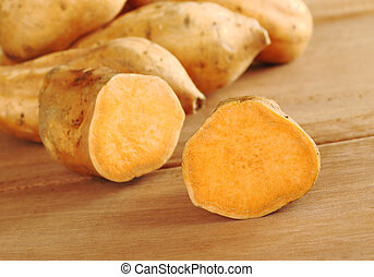 Sweet potato halves (lat. Ipomoea batatas) on wooden surface (Selective Focus, Focus on the half in the front)