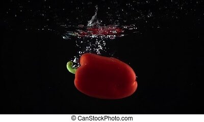 Sweet red pepper falling down in water, black background super slow motion shot