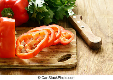 Sweet red pepper sliced on a wooden board, organic food