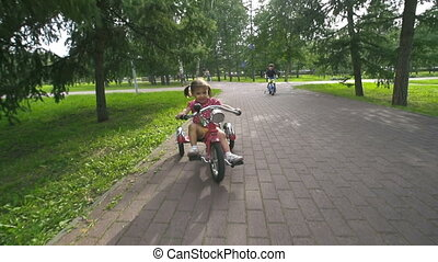 Sweet Riders - Jubilant kids riding bikes in park