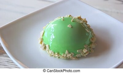 Sweet round cake with green glaze. Delicate appetizing...