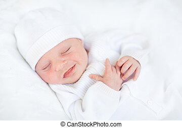 Sweet sleeping smiling newborn baby in a white hat
