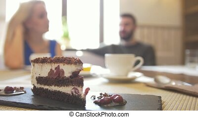 Sweet sliced cake on the plate in front of couple enjoing coffee at the cafe