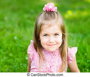Sweet smiling little girl sitting on grass