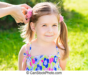 Sweet smiling little girl with her mom's hands making hairstyle (ponytail), outdoor closeup portrait in summer park