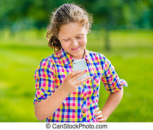 Sweet smiling teenage girl in casual clothes with smartphone in her hand, looking at screen, reading a message, using Facebook in sunny day in summer park
