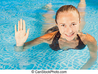 Sweet smiling young girl swimming in the pool