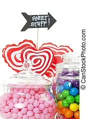 A closeup of part of a candy buffet with a variety of candies in apothecary jars. Shot on white background.